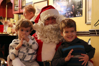 Evan Arms, 2, left, and Hudson Arms, 4, sit on Santa Claus' lap at Mammy's Kitchen in downtown Bardstown during Light Up Bardstown Nov. 25, 2011.