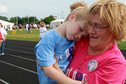 Lou Smith wears a button with a photograph of her son, Michael, with grandson Isaac Riggs, 4, in her arms. Michael Smith died of colon cancer in March 1999, and Lou has been wearing a different button at Relay for Life every year in his memory.