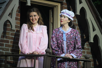 Jane McDowell (Charlotte Campbell) smiles down at Stephen Foster from her balcony, while her mother, portrayed by Jane McIntire, tells Stephen and his friends to quiet down.