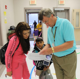 "Buddy Dickerson, known to the kids at Bardstown Primary School as ""Mr. D,"" helps 8-year-old Rachel Perez' mom, Ramona Perez, find out where she's going as they arrive on the first day of classes."