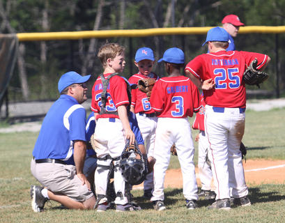 Coaches and players for the Nelson County 7-year-old All-Stars chat between innings of a recent game at Dean Watts Park. Games continue through this week.
