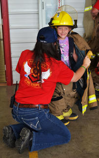 Firefighter Charlene Hess helps dress Alison Sikes in her uniform at the New Hope Fire Department open house Saturday.