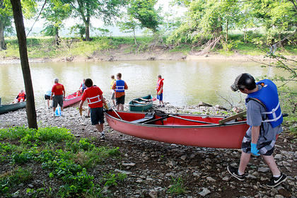 Boy Scouts carry their canoes down to the shore of the Beech Fork River, where nearly 40 people collected a dumpster full of trash along a 5.5-mile stretch of river May 21, 2011, as part of the annual Paddle Pickup hosted by the Bardstown Boaters.