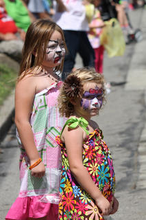 Two sisters with painted faces watch the parade.
