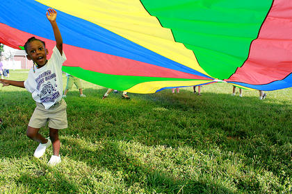 Kindergartner Ta'Nia Calbert struggles to find a new spot around the parachute at Tigerpawlooza, Bardstown Primary School's field day Thursday. Students jumped rope, hoola-hooped, threw water balloons, searched for treasure, hop-scotched and had their faces painted for the end-of-the-year event.