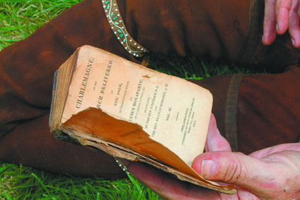 "During a lull in activity, a re-enactor, John Street of Russellville, reads an 1815 copy of ""Charlemagne."""