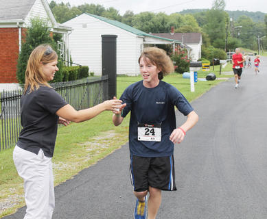 Carla McKay hands a cup of water to a runner in the Iron Horse Festival 5k race in New Haven.
