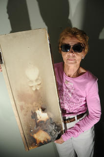 "Cathy Mattingly, Botland holds a piece of what used to be her kitchen cabinet. A fire damaged her kitchen in 2009 when her refrigerator ignited. The fire only damaged her kitchen cabinets, branding a form that Mattingly says resembles a skull. ""I just think it's interesting, I don't think it's haunted though,"" Mattingly said."