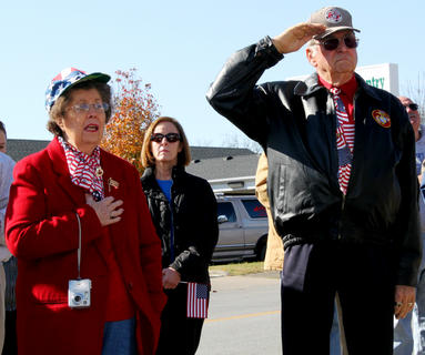 Lou Downs and Tom Downs honor the flag during the ceremony Friday.