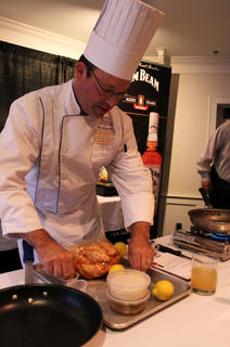 Chef Albert Schmid of Sullivan University teaches a sold out crowd how to cook chicken wings using Booker's bourbon at the Bourbon-Style Cooking School Thursday evening.