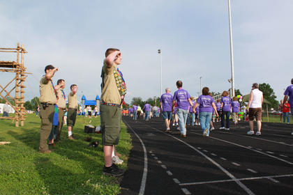 Boy scouts salute cancer survivors during the Survivors' Lap around the Bardstown High School track during the annual Relay for Life fundraiser May 13-14, 2011.