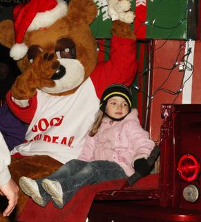 "Haley Coy, 4, sat beside the ""Good Neighbor"" bear on the State Farm float Thursday night."