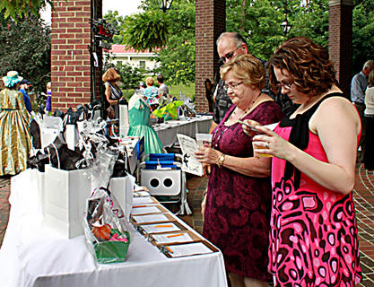 """John and Jeannine Warren, parents of Stephen Foster Drama Association Artistic Director Johnny Warren, and daughter LeAnne Richardson check out the silent auction items at the Opening Night Gala & Garden Party for """"The Stephen Foster Story"""" June 11."""