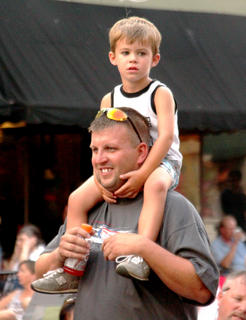 Blake Mudd, 3, Bardstown, gets a ride from his dad Michael Mudd, during the 10th annual street concert.