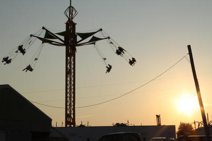 The sun sets Thursday at the fair. The heat index was well over 100 but some fairgoers caught a breeze while riding the swings.