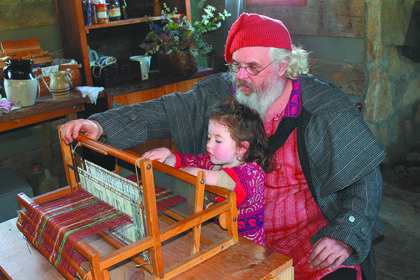 Mike Hainlen of Greentown, Ind., shows his granddaughter,  4-year-old Cassidy Grinslade, how to work a weaver's loom.