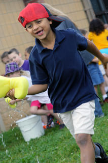 Bardstown Primary kindergartener Will Fleenor runs with a sponge soaked in water during a race at Tigerpawlooza Friday, May 24.