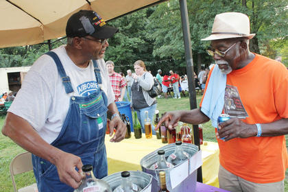 Norris Shelton, right, asks to try some of Bob Johnson's muscadine wine. The muscadine was the winner at this year's Buttermilk Days homemade wine contest. Johnson, of Louisville, has won it four years in a row.