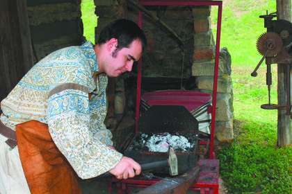 A young blacksmith, Patrick Smith of Shepherdsville, demonstrates his craft.