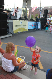 Belah Green, 19 months, and grandmother Marian Ferguson enjoy the music of Pat Kirtley. Adults and children alike enjoyed the music of such musicians as guitarist Kirtley, onstage, and Bardstown/Australian folk-rock musician Pauly Zarb's band at Pauly Zarb's 2011 Bardstown Street Concert on North Third Street in Bardstown July 9. Bardstown Main Street Manager Rita Riley estimated the event drew a crowd of 2,500 or more.