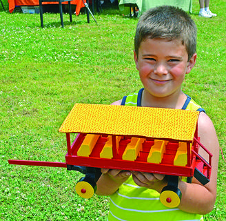 Aidan Greenwell, of Bardstown, shows off his newly purchased, hand-crafted wagon at the Kentucky Dam Village State Resort Park Arts and Crafts Show Saturday. Aidan got the wagon for half price, spending $15 of his own money.