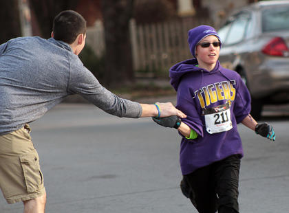 Eli Nowaskie, 10, gets encouragement during his participation in the third annual Forget Me Not Fun Run Saturday.