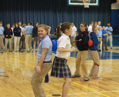 Sixth-grader Izzy Neel, St. Joseph School, and junior Megan Wimpsett, Bethlehem High School, compete for the blue team in the Back Ball Relay, part of the celebration of Catholic Schools Week hosted at Bethlehem High School Feb. 3 with St. Joseph and St. Catherine Academy in attendance.