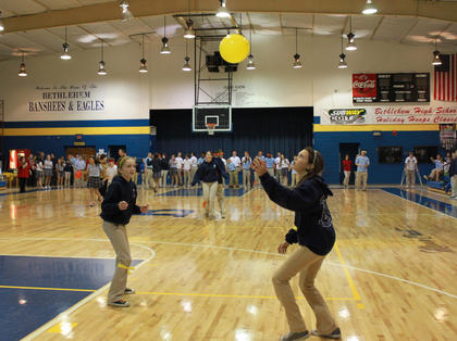 Sixth-grader Cameron Boone, left, and eighth-grader Sidney Culver, both of St. Catherine Academy, pass a balloon for the yellow team in the Back Ball Relay, part of the celebration of Catholic Schools Week hosted at Bethlehem High School Feb. 3 with St. Catherine and St. Joseph School in attendance.