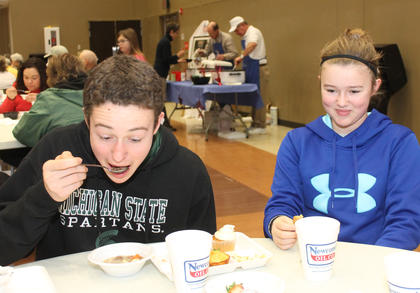 Ben Hite takes a bite of steaming soup while his sister, Ellie Hite waits for his reaction. Their family attended the Souper Bowl of Caring at St. Joe to raise money for St. Vincent de Paul's food pantry.