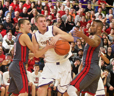 Bardstown's Tyler Holsclaw yanks a rebound away from Taylor County's Brandon Berry, right. The Tigers fell 58-39 to the Cardinals in Tuesday's 5th Region championship.