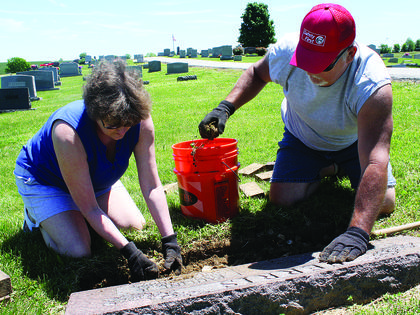 Marvin and Denisa Ferris replace rocks and bricks in front of a grave belonging to Marvin's mother, Pauline Ferris, who drowned 41 years ago in the Ohio River. The grave is one of many in the Ferris family to be found at Big Springs Cemetery in Bloomfield.
