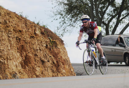 A bicyclist makes a sharp turn on Pottershop Road during My Old Kentucky Home Bike Tour Saturday.