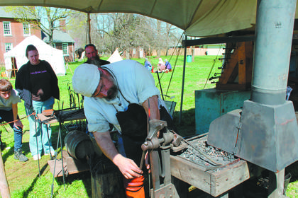 A blacksmith,  Mark Thomas, demonstrates his craft.