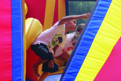 Children race through an inflatable obstacle course at a Back to School Block Party.