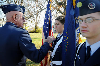 Gennasea Fain and Josh Morgan stand at attention while Major Edward Jett fixes Fain's collar before ceremonies at Bloomfield Memorial Park Veteran's Day.