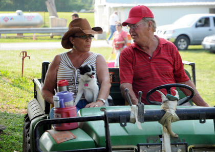 Peggy Boone and John Boone ride an all terrain vehicle at White Acres Campground with their dog, Suzie Q.
