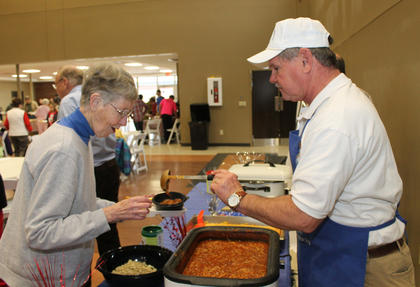 Bobby Settles of the Knights of Columbus serves chili to one of the guests of the Souper Bowl Saturday at St. Joe.