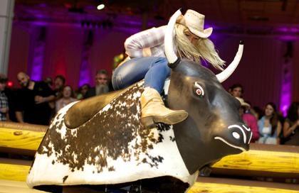 A guest tests her bull-riding skills at the Boots and Bourbon event Thursday night of the 2014 Kentucky Bourbon Festival.