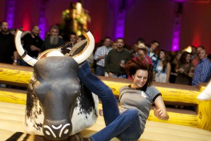 A guest at learns the limits of her bull-riding skills at the Boots and Bourbon event Thursday night of the 2014 Kentucky Bourbon Festival.
