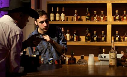 A bartender takes a guest's order at the Boots and Bourbon event Thursday night of the 2014 Kentucky Bourbon Festival.