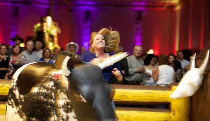 A guest learns the limits of her bull-riding skills at the Boots and Bourbon event Thursday night of the 2014 Kentucky Bourbon Festival.