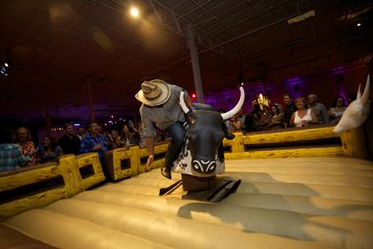 A guest learns the limits of his bull-riding skills at the Boots and Bourbon event Thursday night of the 2014 Kentucky Bourbon Festival.