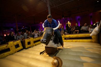 A guest loses his hat  as he is helped onto the mechanical bull at the Boots and Bourbon event Thursday night of the 2014 Kentucky Bourbon Festival.