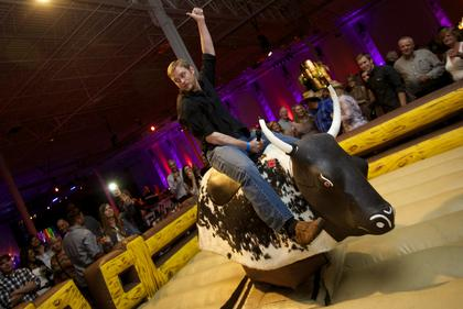 A guest signals he is ready to test his bull-riding skills at the Boots and Bourbon event Thursday night of the 2014 Kentucky Bourbon Festival.