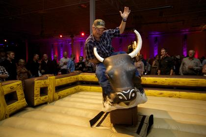 A guest tests his bull-riding skills at the Boots and Bourbon event Thursday night of the 2014 Kentucky Bourbon Festival.