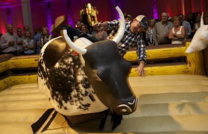 A guest at learns the limits of his bull-riding skills at the Boots and Bourbon event Thursday night of the 2014 Kentucky Bourbon Festival.
