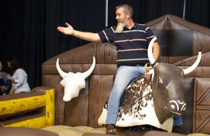A guest prepares to test his bull-riding skills at the Boots and Bourbon event Thursday night of the 2014 Kentucky Bourbon Festival.