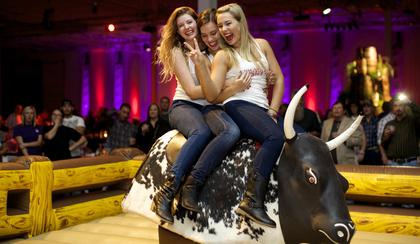 Wild Turkey's American Honey Girls prepare to test their bull-riding skills at the Boots and Bourbon event Thursday night of the 2014 Kentucky Bourbon Festival.