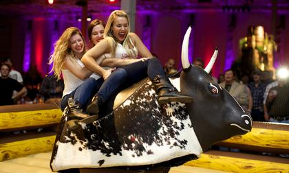 Wild Turkey's American Honey Girls take a spill off the mechanical bull at the Boots and Bourbon event Thursday night of the 2014 Kentucky Bourbon Festival.