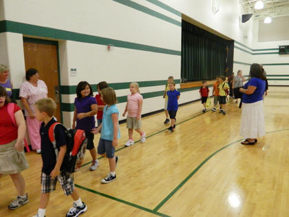 Boston School students line up in the gymnasium to be led to their first day of class. The school provides education to children in kindergarten through 8th grade in Boston under Principal Tammy Newcome.